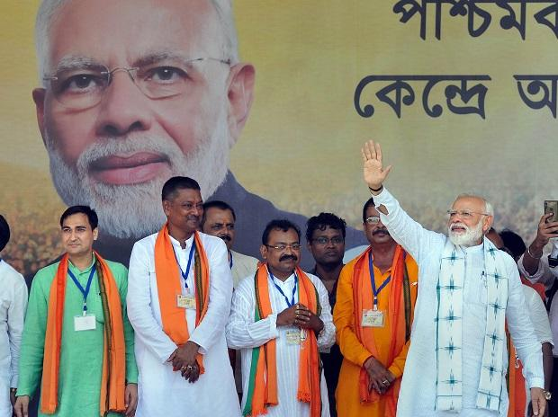 Prime Minister Narendra Modi waves at supporters during an election campaign rally for the Lok Sabha polls, at Haldia in East Midnapore district of West Bengal