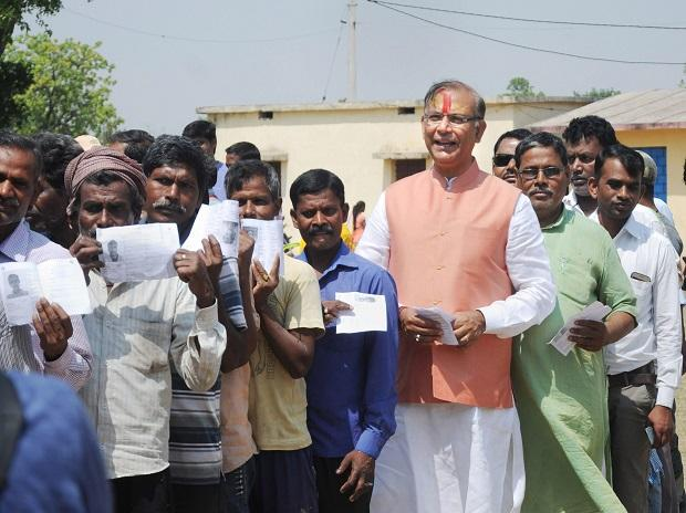 Union Minister and BJP candidate for Hazaribagh,Jayant Sinha, shows his voter ID card as he waits in a queue to cast his vote