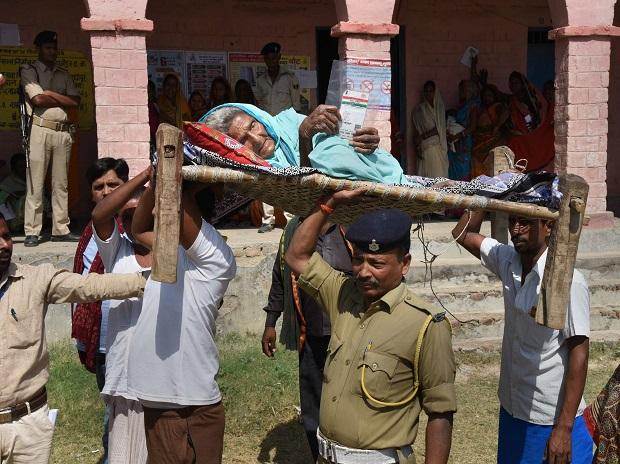 Security personnel carry an elderly woman to a polling station to cast vote  at Hajipur in Vaishali district
