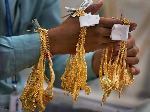 A sales person shows gold ornaments at a jewellery shop, on the occasion of 'Akshaya Tritiya', in Chennai on Tuesday