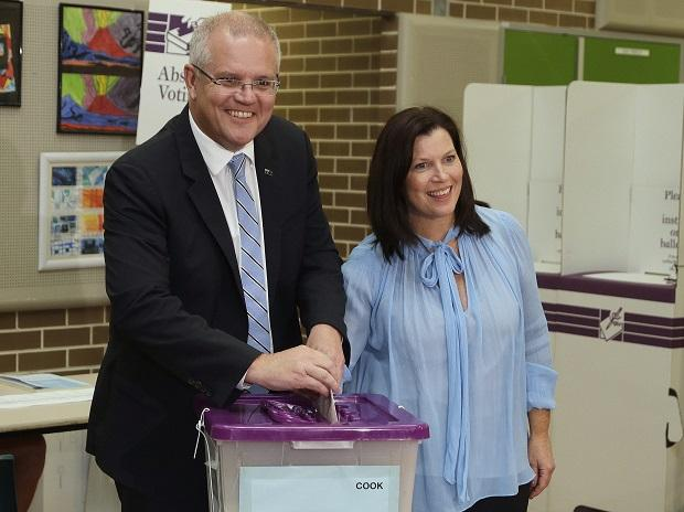 Australian Prime Minister Scott Morrison (left) is assisted by his wife, Jenny, as he casts his ballot in a federal election in Sydney 	 	Photo: AP/PTI