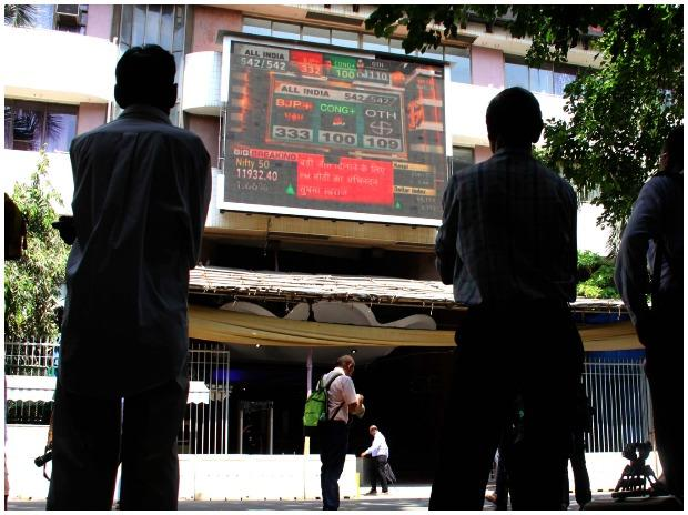 People watches stock market screen display on the facade of the Bombay Stock Exchange