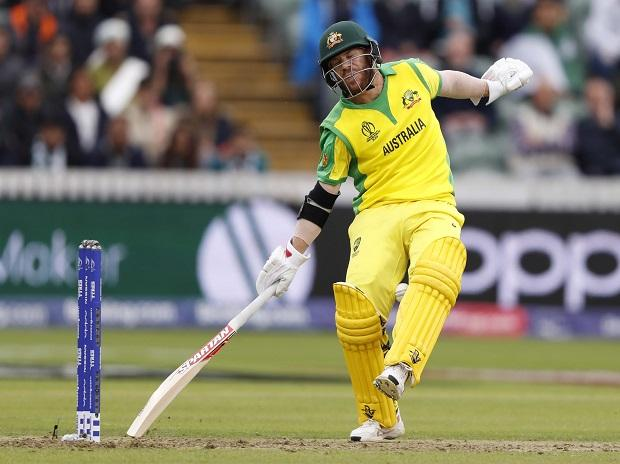 Australia's David Warner reacts as the ball is thrown towards his stumps in an attempted run out