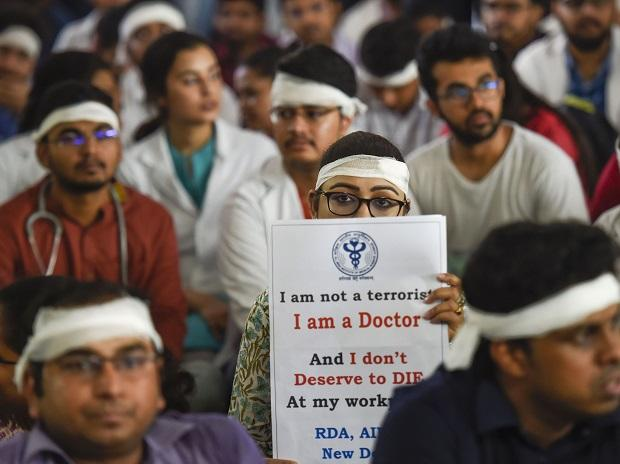 Members of Resident Doctors Association (RDA) of AIIMS wearing bandages on their heads protest to show solidarity with their counterparts in West Bengal