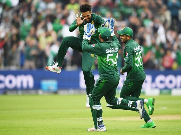 Pakistan's bowler Mohammad Amir, left, jumps as he celebrates with teammates after dismissing New Zealand's batsman Martin Guptill for 5 runs
