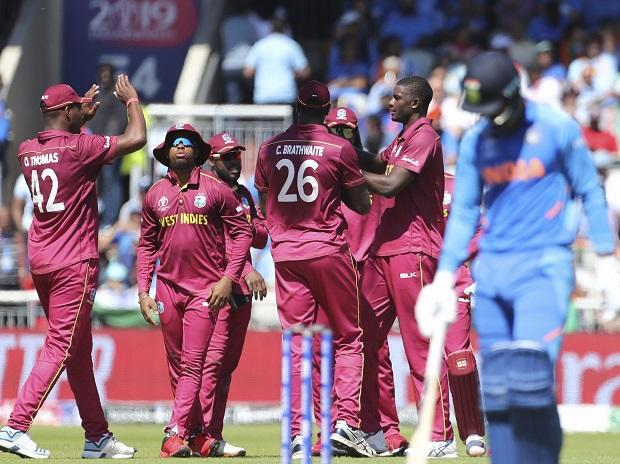 West Indies' captain Jason Holder, second right, celebrates with teammates the dismissal of India's K.L. Rahul, right