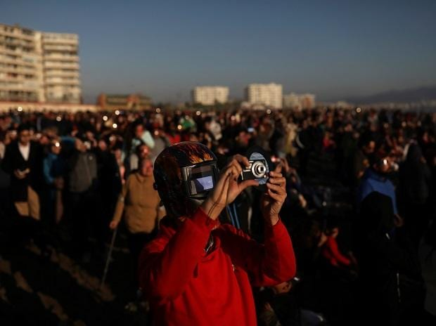 A mas wears a mask to observe the solar eclipse at La Serena, Chile