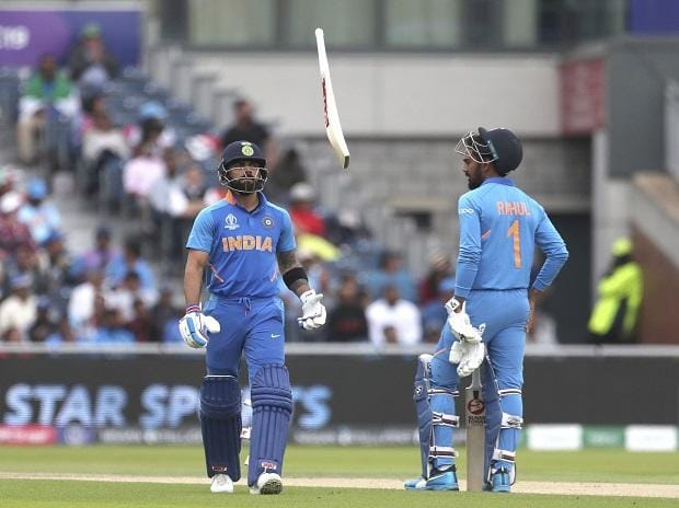 India's captain Virat Kohli, left, throws his bat in frustration after being dismissed by New Zealand's Trent Boult