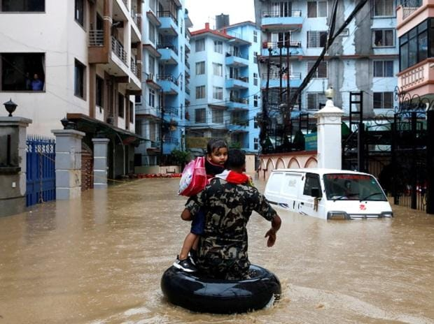A member of Nepalese army carrying a child walks along the flooded colony in Kathmandu, Nepal Photo: Reuters