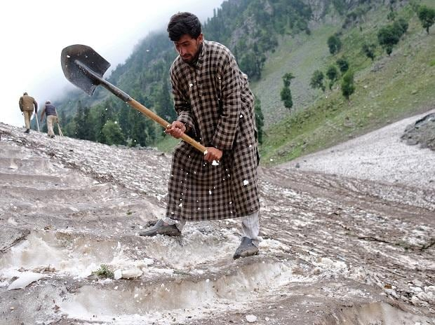 A Kashmiri Muslim man cuts snow to make way for Hindu pilgrims to trek to reach the holy Amarnath cave shrine, where they worship an ice stalagmite that Hindus believe to be the symbol of Lord Shiva, near Pahalgam in the Kashmir region