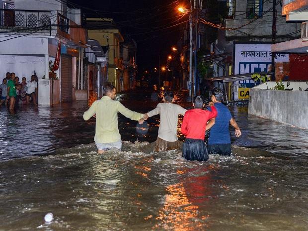 People wade across a flooded street following heavy monsoon rain, in Jabalpur
