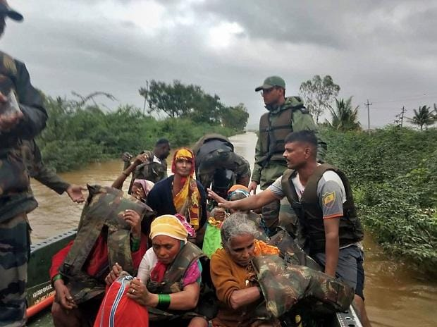 Flood victims are rescued on a boat during a coordinated relief and rescue operations by Army Forces in flood-affected areas of Belgaum district