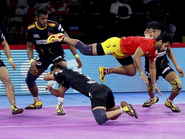 Gujarat Fortune Giants (In Red) and Telugu Titans players in action during their match at 7th season of Pro-Kabaddi League