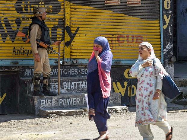 Women walk past a CRPF person standing guard in a street in Srinagar, Thursday