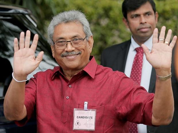Sri Lanka People's Front party presidential election candidate and former wartime defence chief Rajapaksa waves at media as he arrives to hand over nominations papers at the election commission in Colombo