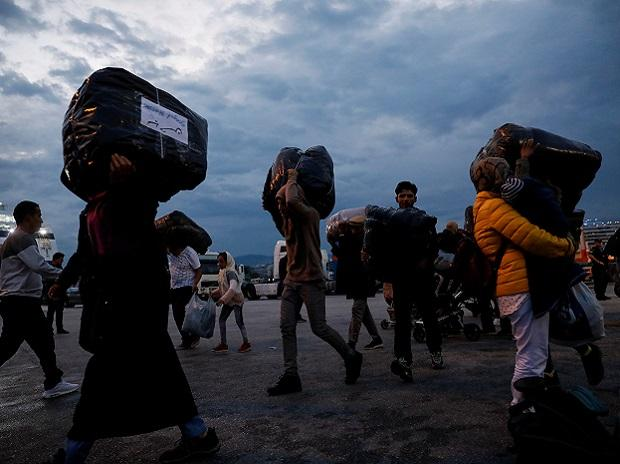 Refugees and migrants carry their luggage as they arrive on a passenger ferry from the island of Lesbos at the port of Piraeus</headline>  <by>GIORGOS MOUTAFIS