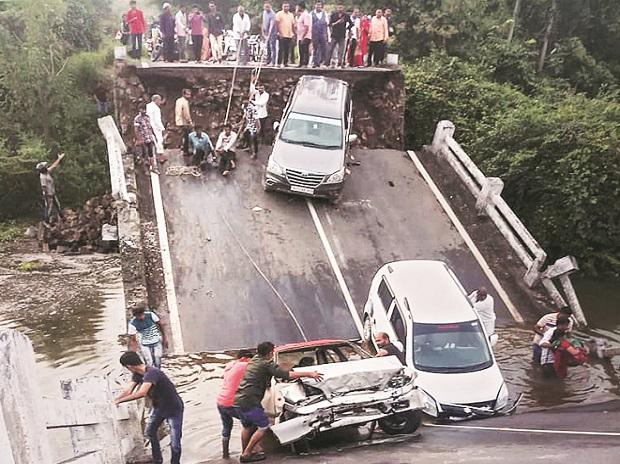 Vehicles stuck in the gaps after slabs of a 60-feet-long bridge collapsed in Junagadh district, Gujarat. Photo: PTI