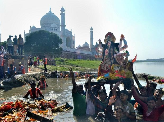 Devotees immerse an idol of goddess Durga on River Yamuna in the backdrop of Taj Mahal, in Agra in 2019. (PTI Photo)