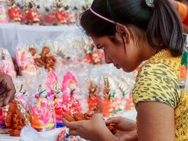 A young woman buys an idol of goddess Laxmi on the occasion of Dhanteras festival ahead of Diwali, in Varanasi