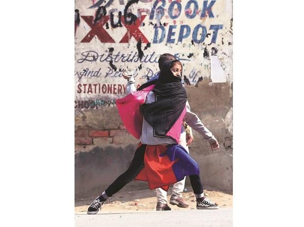 A girl throws a stone towards policemen during a protest in Srinagar on Tuesday