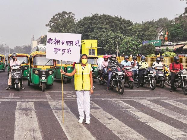 A volunteer displays a placard asking people to obey the odd-even rule, in New Delhi	Photo: PTI