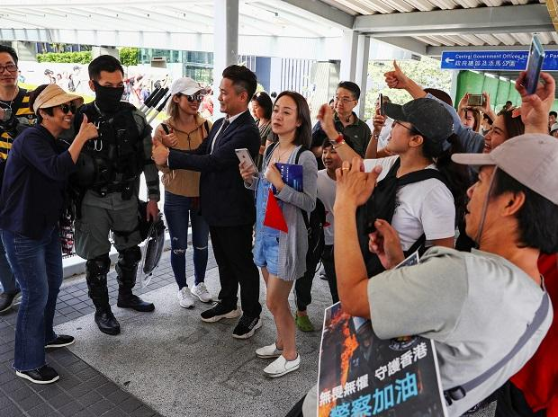 A pro-government supporter and a riot policeman flash thumbs up during a rally at the Legislative Council (LegCo) building in Hong Kong, China, November 16, 2019 | Reuters