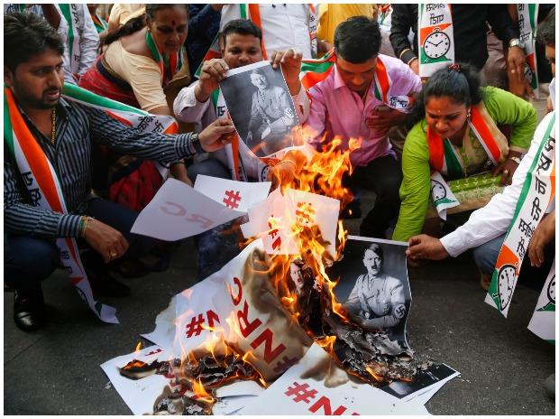 NCP leader Jitendra Awhad with party supporters burns posters in Thane
