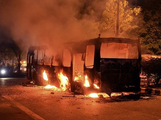 A DTC bus set on fire following protests near Mathura Road, in New Delhi