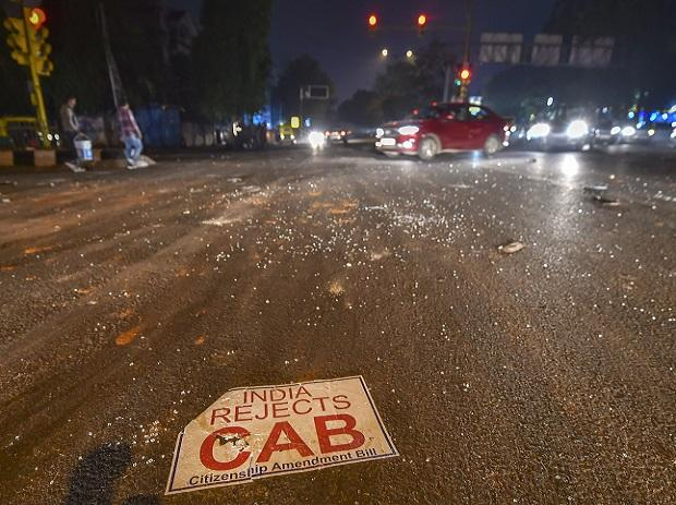 Shattered glass from a damaged vehicle spreads across a roadway after protest turned violent at Mathura Road, in New Delhi