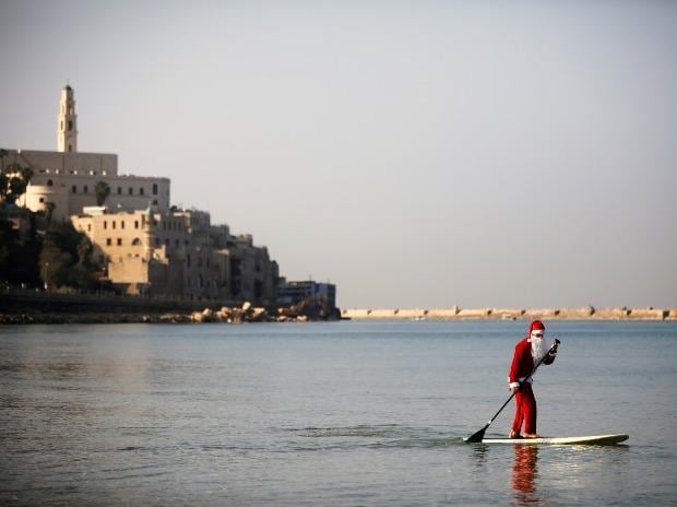 A man wearing a Santa Claus costume paddles on a SUP board in the Mediterranean Sea as Jaffa port  is seen in the background during an event organised by the Tel Aviv municipality, off the coast of Tel Aviv, Israel.