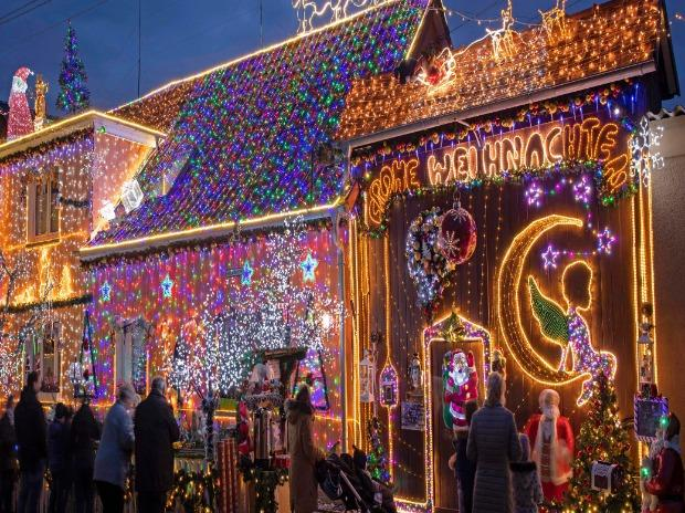 People stand in front of the decorated Christmas house of Mario Leicht in Walschleben, central Germany.
