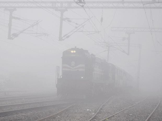 A trains runs through a dense layer of fog on a cold and wintry morning