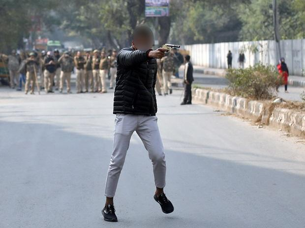 An unidentified man brandishes a gun during a protest against a new citizenship law outside the Jamia Millia Islamia university in New Delhi. Photo: Reuters