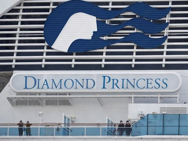 Masked passengers look on from onboard the coronavirus-hit Diamond Princess cruise ship docked at Yokohama Port, south of Tokyo, Japan. (Photo: Reuters)