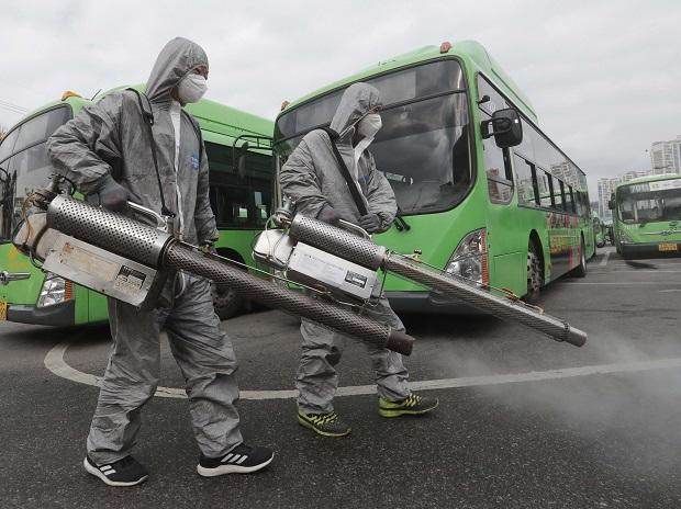 Workers wearing protective suits spray disinfectant as a precaution against the coronavirus at a bus garage in Seoul | PTI