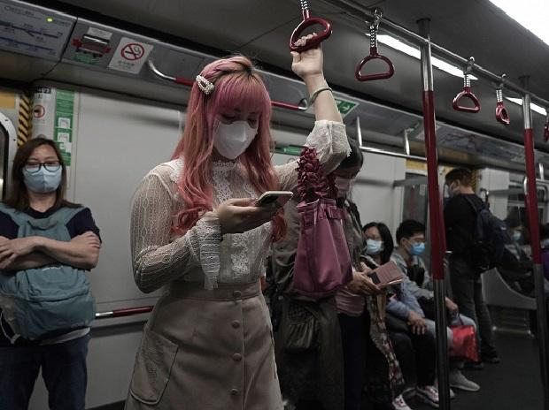 A woman wearing a face mask as a precaution against the COVID-19 while using smartphone in a subway train in Hong Kong | PTI