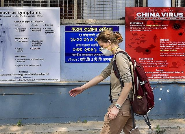 Kolkata: A tourist wears a mask as she walks past the posters on awareness towards COVID-19 during her arrival for a health checkup, at ID & BG Hospital in Kolkata. (PTI Photo/Swapan Mahapatra)