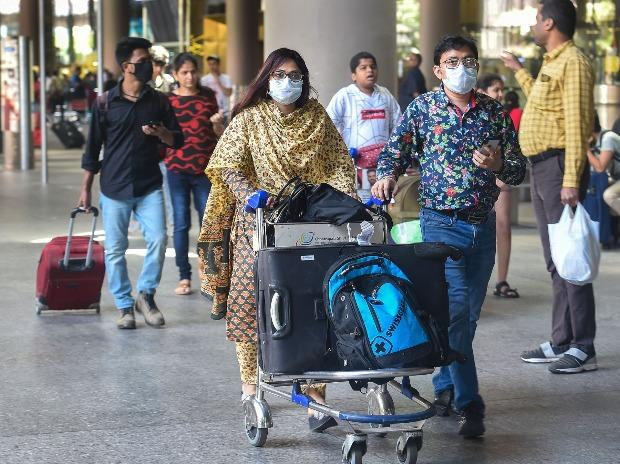Fight passengers, wearing protective masks as precautionary measure against the coronavirus, at the international airport in Mumbai