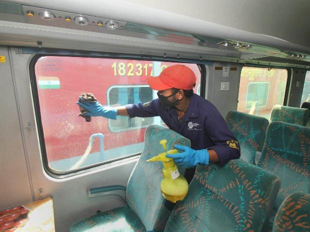A railway worker disinfect a coach of a train in the wake of coronavirus pandemic, in Guwahati