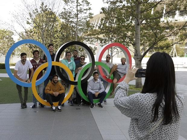 A group of students from Uruguay pose for a souvenir picture on the Olympic Rings set outside the Olympic Stadium in Tokyo. Photo: AP | PTI