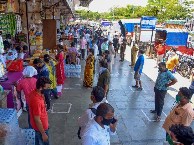 People maintain social distancing while standing in queues to buy essential items from shops at APMC market, during ongoing COVID-19 lockdown, in Navi Mumbai