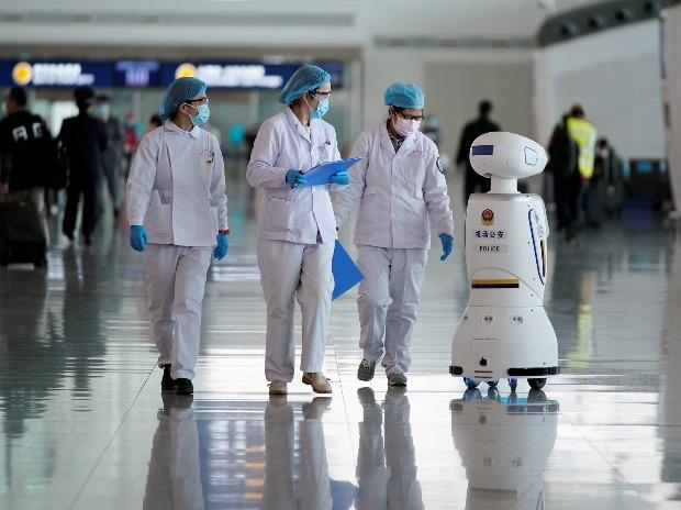 Medical workers walk by a police robot at the Wuhan Tianhe International Airport. Photo: Reuters