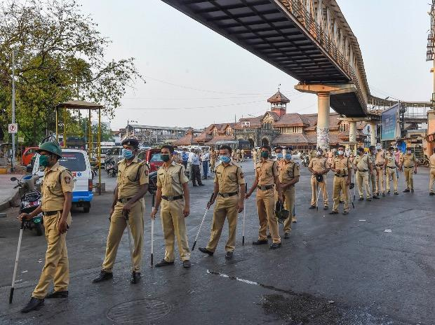 Police officials stand in a queue to get sanitised after dispersing hundreds of stranded migrant workers from outside the Bandra Railway Station in Mumbai. Photo: PTI