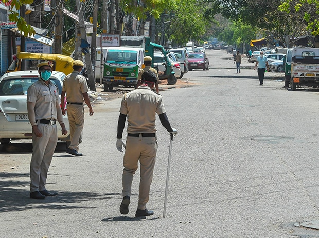 Security personnel stand guard on a deserted road at C block Jahangirpur area, identified as COVID-19 hotspot during the nationwide lockdown to curb the spread of coronavirus, in New Delhi. Photo: PTI