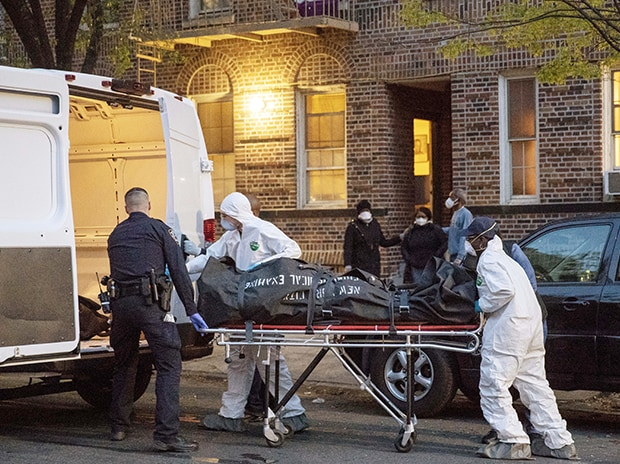 An officer from the New York Police Department helps workers carry a body out of a house amid the coronavirus disease. Photo: Reuters