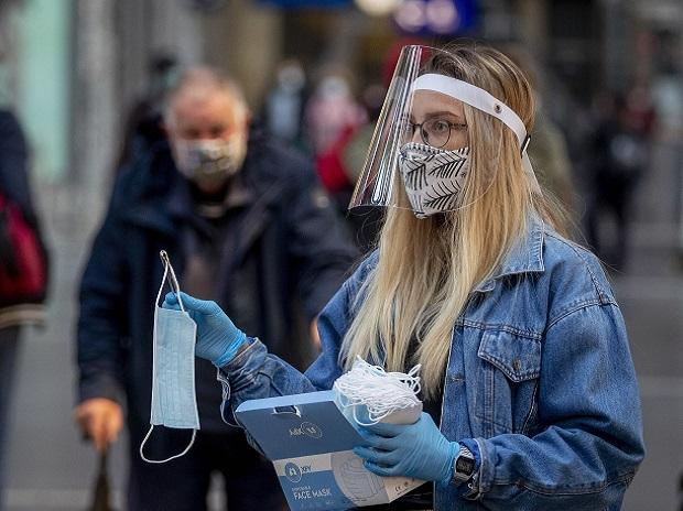 Frankfurt:  A woman working for the regional public transport company offers face masks in the main train station in Frankfurt, Germany, Monday, April 27, 2020. AP/PTI