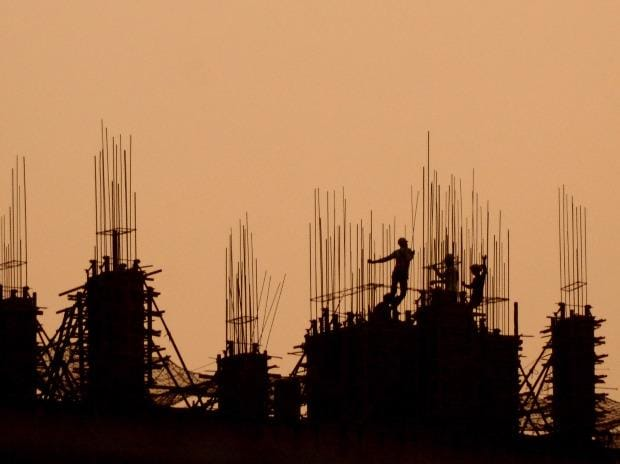 Workers are silhouetted against the setting sun at a construction site during the nationwide lockdown, on the eve of  Labour Day, in Navi Mumbai