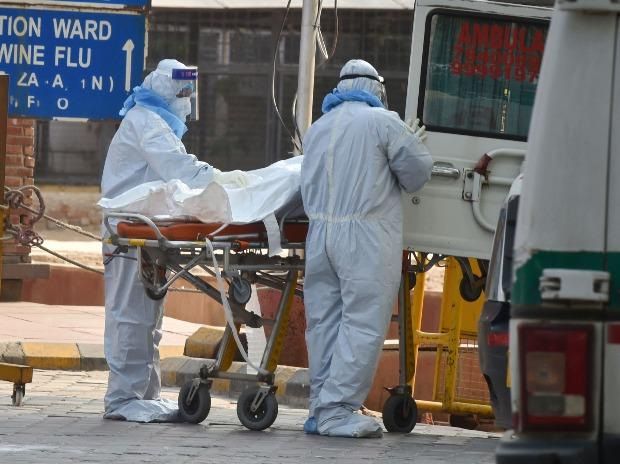 Health workers wearing protective suits shift to a van the body of a coronavirus victim, at LNJP Hospital in New Delhi