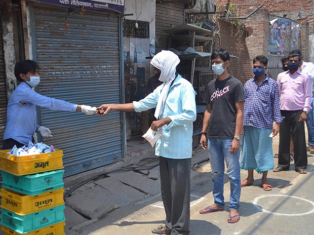 People practice social distancing as they queue up to buy milk packets from a vendor, during ongoing Covid-19 lockdown in Varanasi. Photo: PTI