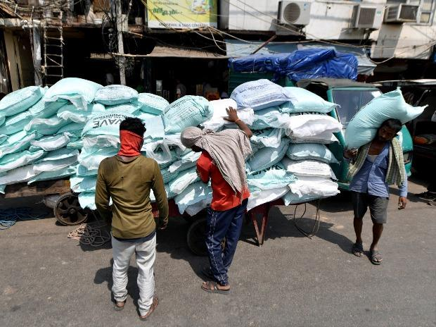 Workers load filled sacks on a cart at Shardhanand Market during the nationwide lockdown, near GB Road in New Delhi